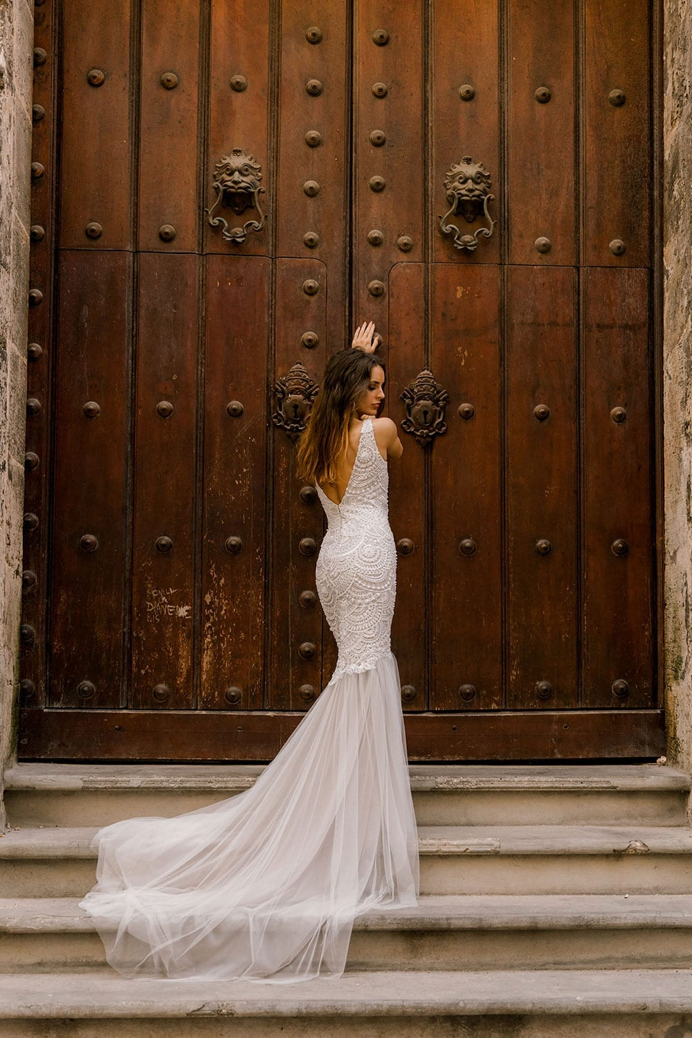 Model wearing Vinka Design Carlotta Wedding Dress, a V-Neck Beaded Mermaid Dress on the streets of Havana in front of an old wooden door with dress flowing down the steps