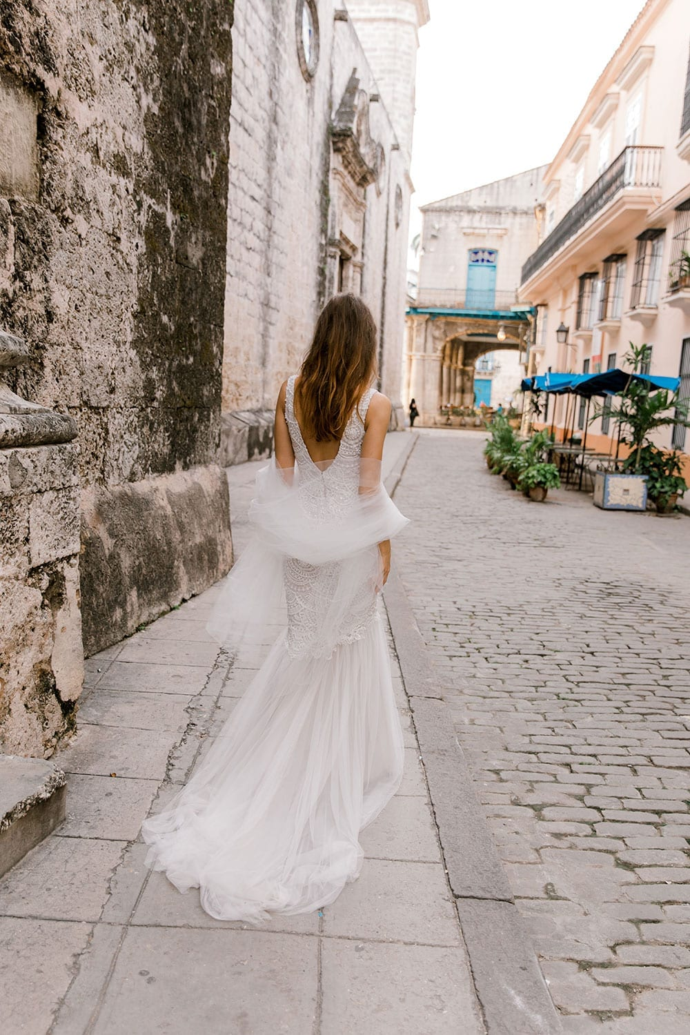 Model wearing Vinka Design Carlotta Wedding Dress, a V-Neck Beaded Mermaid Dress on the streets of Havana in front of an old wooden door with dress flowing down the stepswalking through the streets of Havana with the dress flowing behind