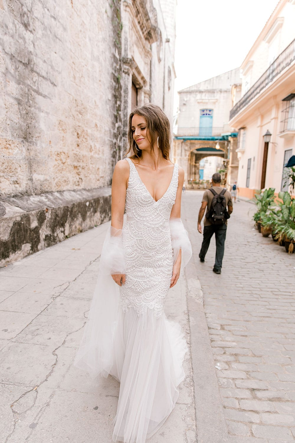 Model wearing Vinka Design Carlotta Wedding Dress, a V-Neck Beaded Mermaid Dress on the streets of Havana in front of an old wooden door with dress flowing down the stepswalking through the streets of Havana