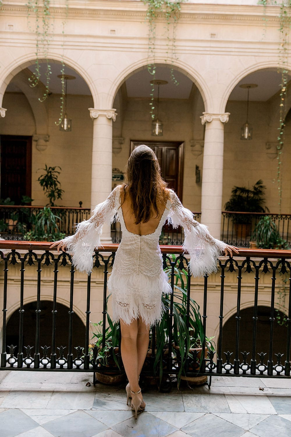 Model wearing Vinka Design Chanel Wedding Dress, a Beaded French Lace Wedding Gown in building archways of Havana