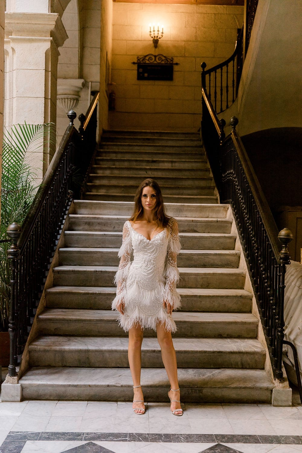Model wearing Vinka Design Chanel Wedding Dress, a Beaded French Lace Wedding Gown in beautiful building with long stairway in Havana