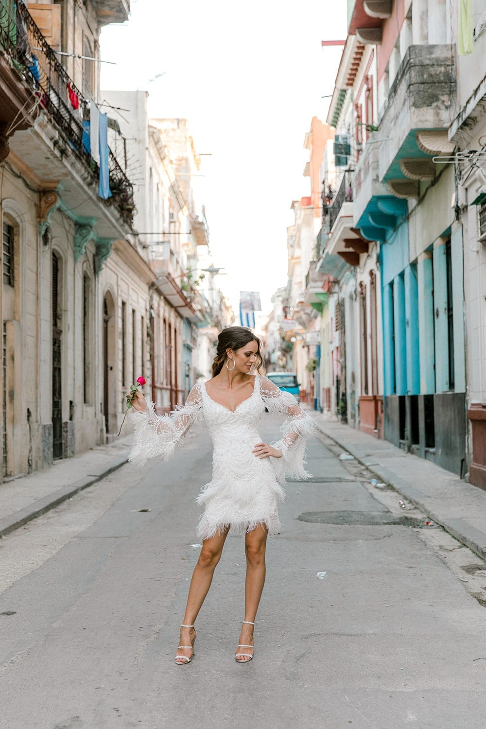 Model wearing Vinka Design Chanel Wedding Dress, a Beaded French Lace Wedding Gown in beautiful streets of Havana
