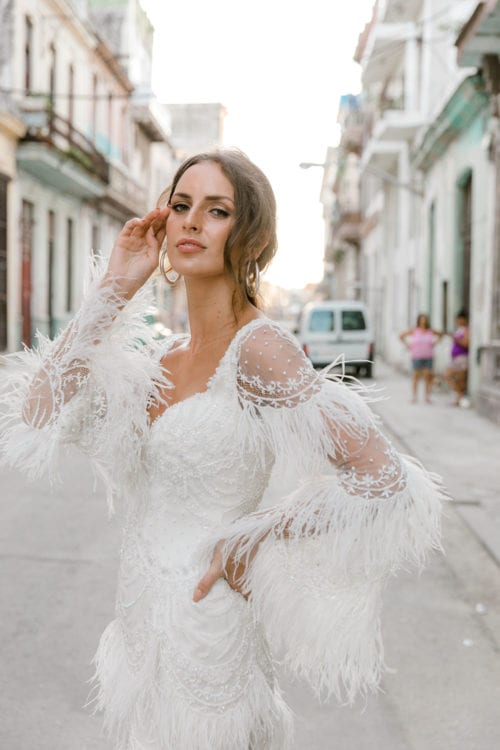 Model wearing Vinka Design Chanel Wedding Dress, a Beaded French Lace Wedding Gown facing camera with hand to head in beautiful streets of old Havana