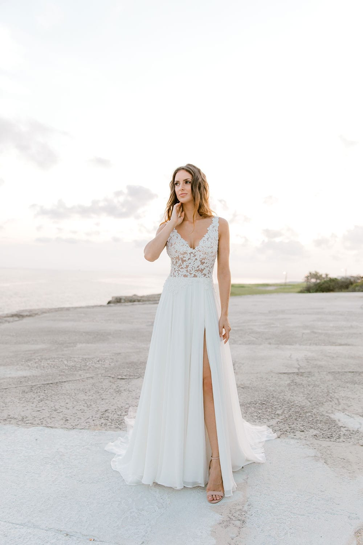 Model wearing Vinka Design Clara Wedding Dress, a Silk Chiffon Beaded Lace Wedding Gown next to the ocean in Havana