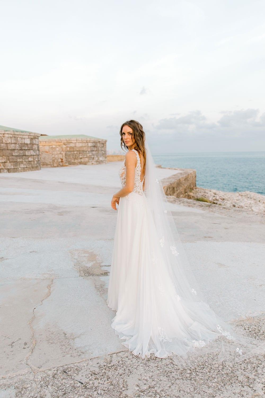 Model wearing Vinka Design Clara Wedding Dress, a Silk Chiffon Beaded Lace Wedding Gown next to the ocean in Havana with dress facing away