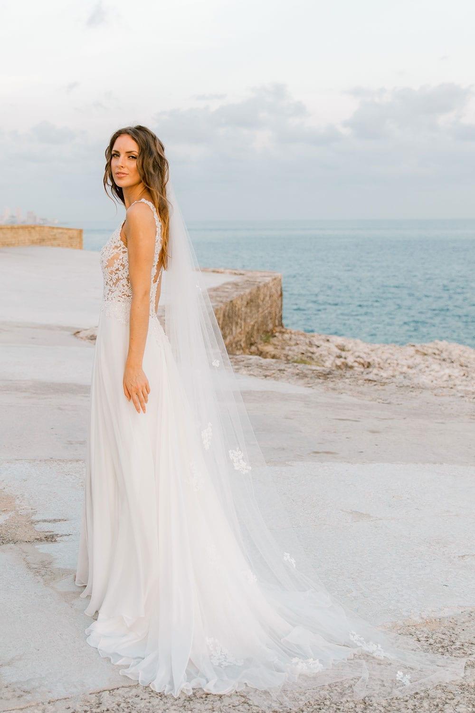 Model wearing Vinka Design Clara Wedding Dress, a Silk Chiffon Beaded Lace Wedding Gown next to the ocean in Havana facing away with dress flowing