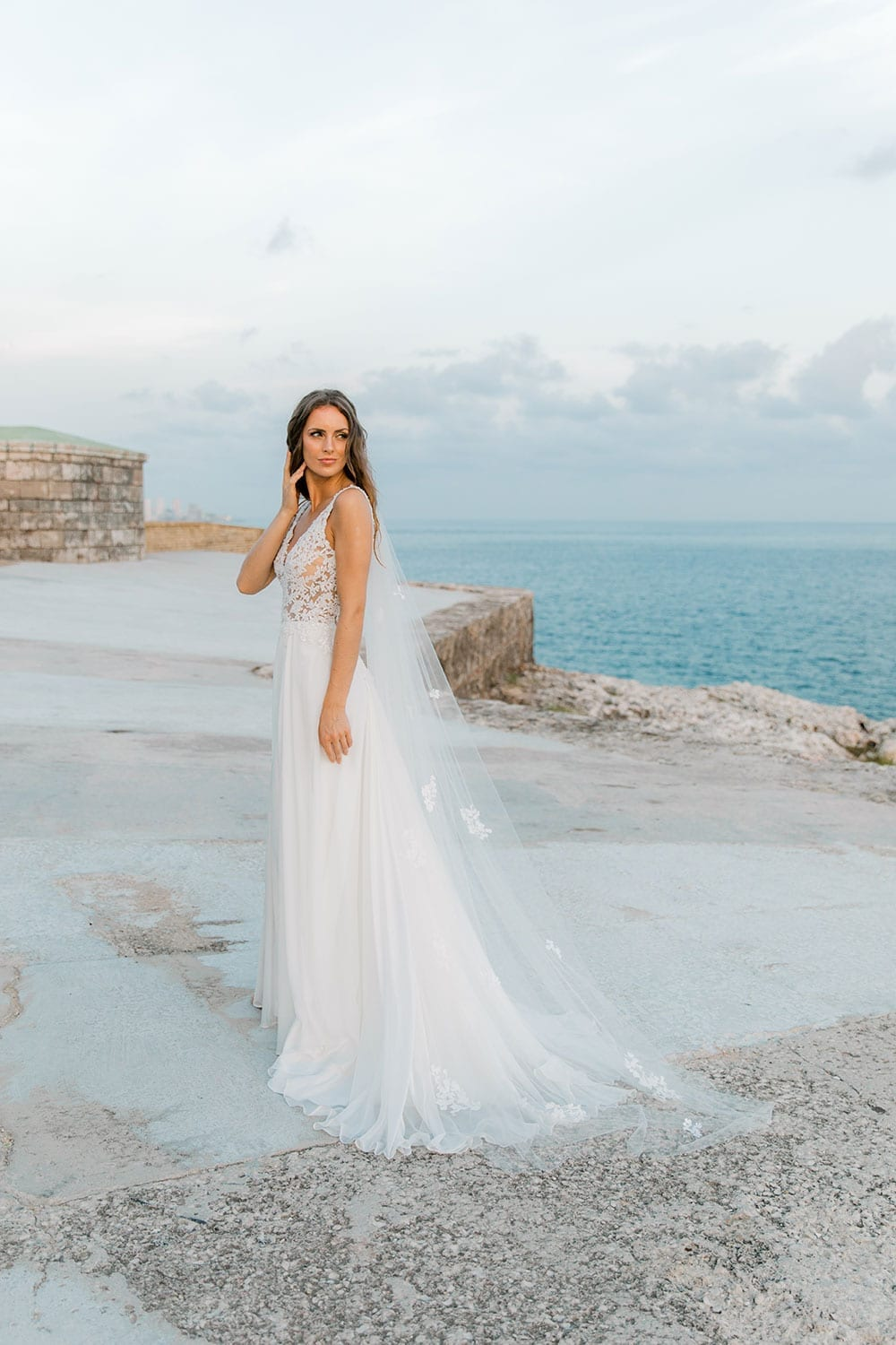 Model wearing Vinka Design Clara Wedding Dress, a Silk Chiffon Beaded Lace Wedding Gown next to the ocean in Havana side angle with dress flowing