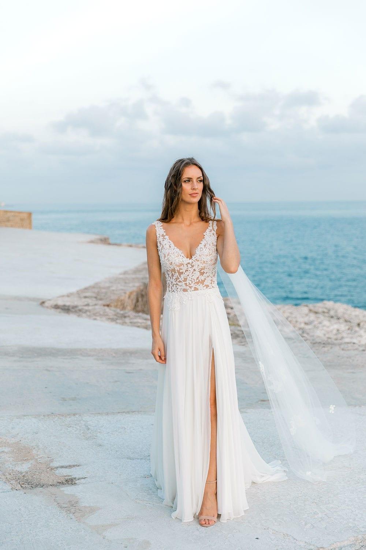 Model wearing Vinka Design Clara Wedding Dress, a Silk Chiffon Beaded Lace Wedding Gown next to the ocean in Havana showing split of dress at front