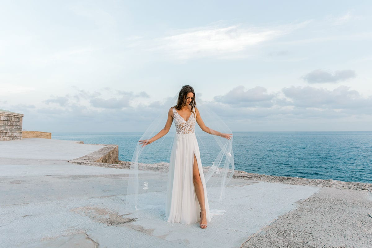 Model wearing Vinka Design Clara Wedding Dress, a Silk Chiffon Beaded Lace Wedding Gown next to the ocean in Havana with dress lifted by arms out wide
