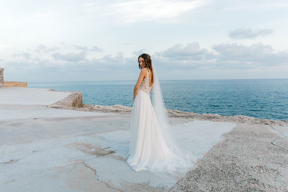 Model wearing Vinka Design Clara Wedding Dress, a Silk Chiffon Beaded Lace Wedding Gown next to the ocean in Havana looking to the distance