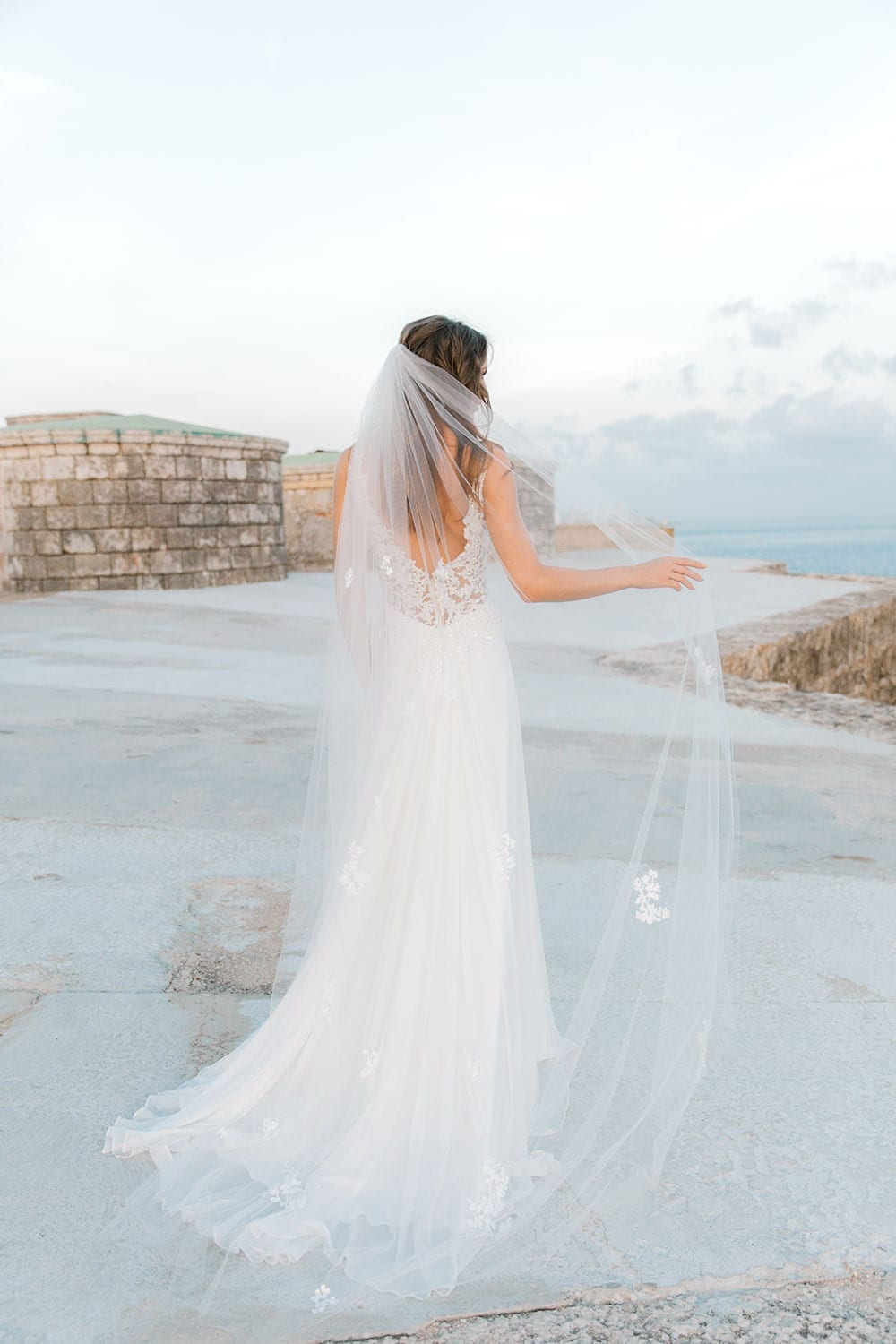 Model wearing Vinka Design Clara Wedding Dress, a Silk Chiffon Beaded Lace Wedding Gown next to the ocean in Havana facing away with dress and veil flowing