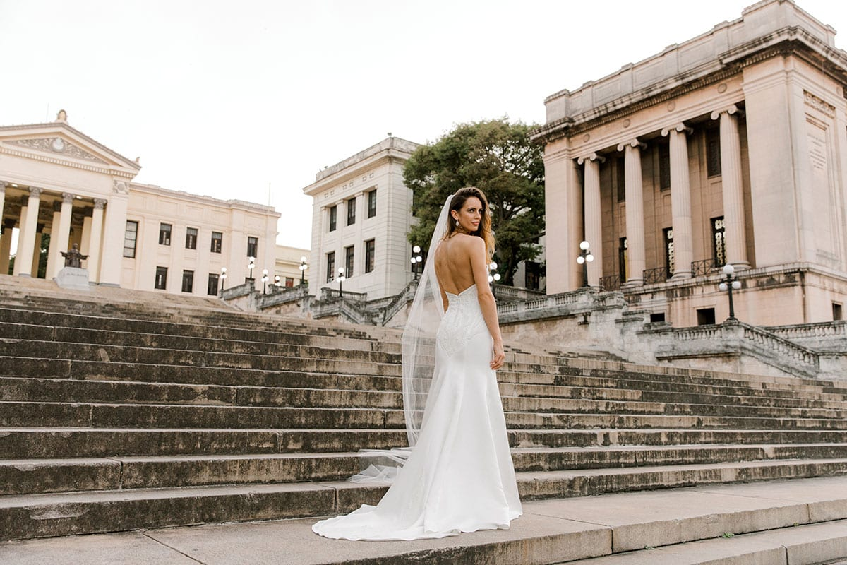 Model wearing Vinka Design Elsa Wedding Dress, a Satin Princess Line Wedding Gown with bodice on steps in front of a building in Havana
