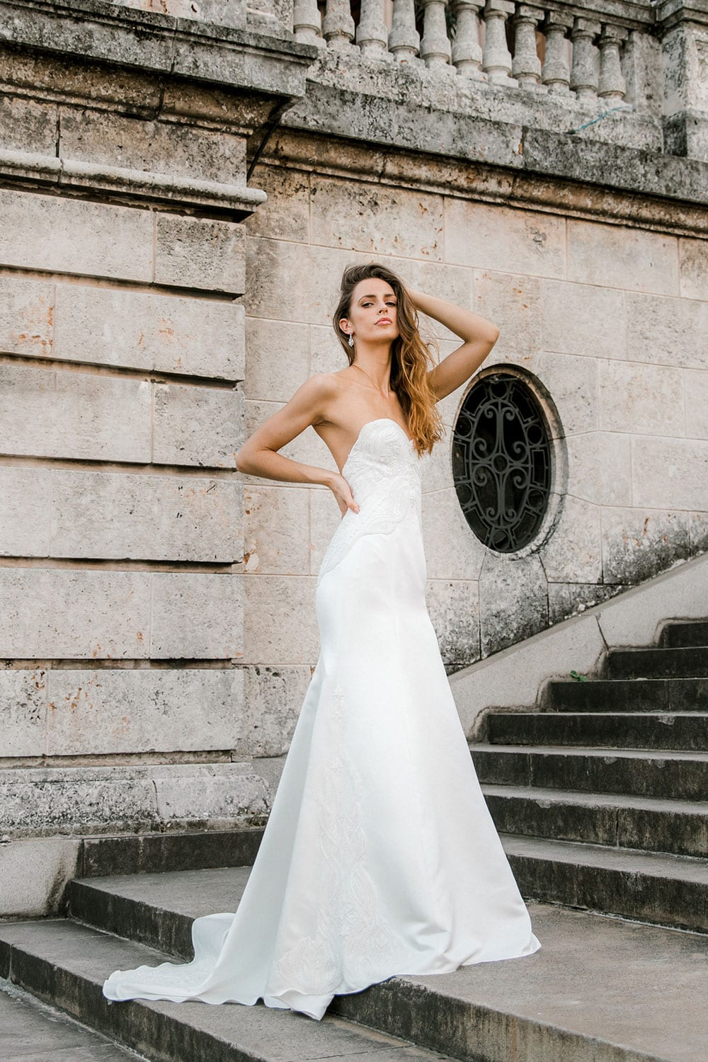 Model wearing Vinka Design Elsa Wedding Dress, a Satin Princess Line Wedding Gown with bodice on steps in the heart of Havana