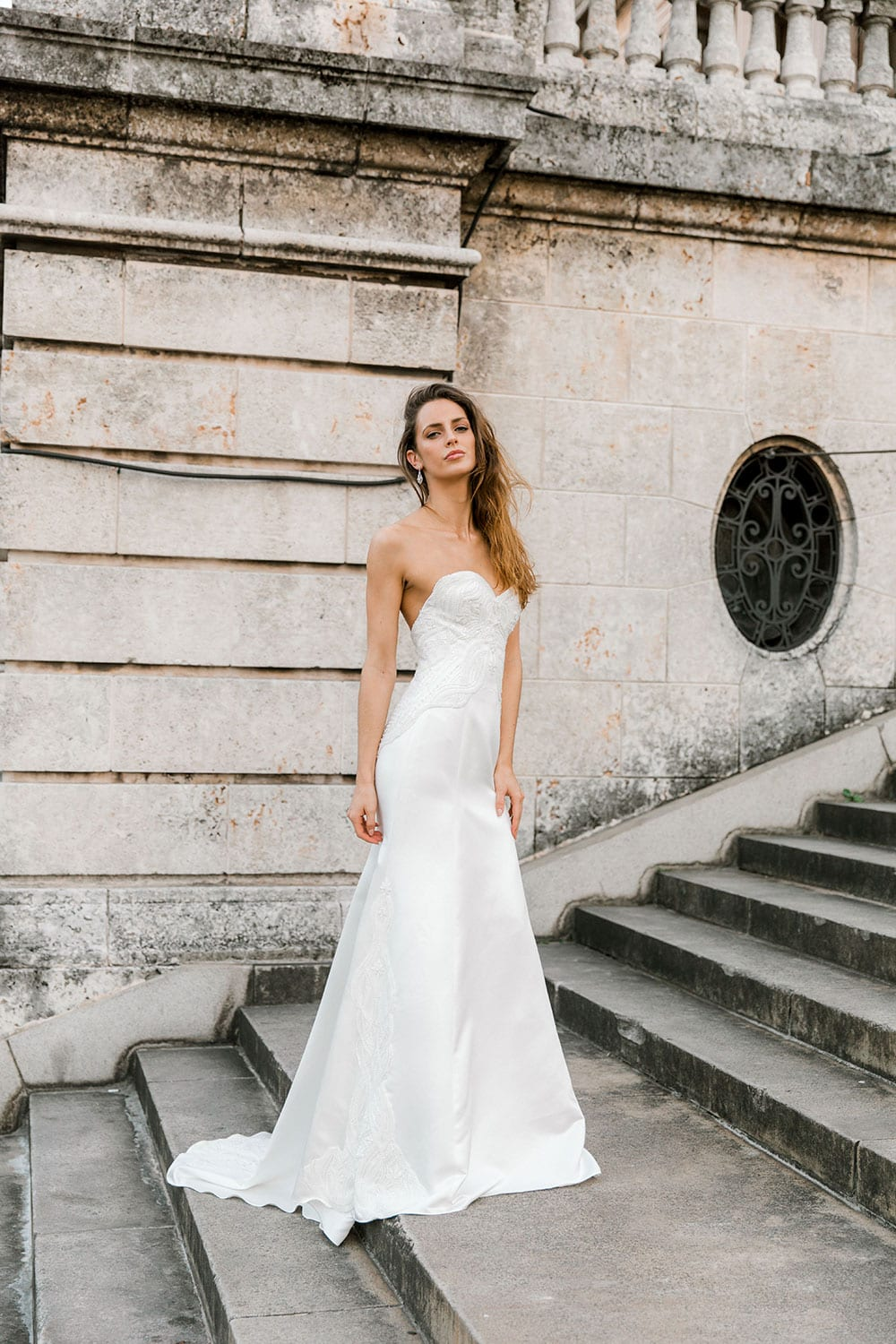 Model wearing Vinka Design Elsa Wedding Dress, a Satin Princess Line Wedding Gown with bodice on steps in Havana