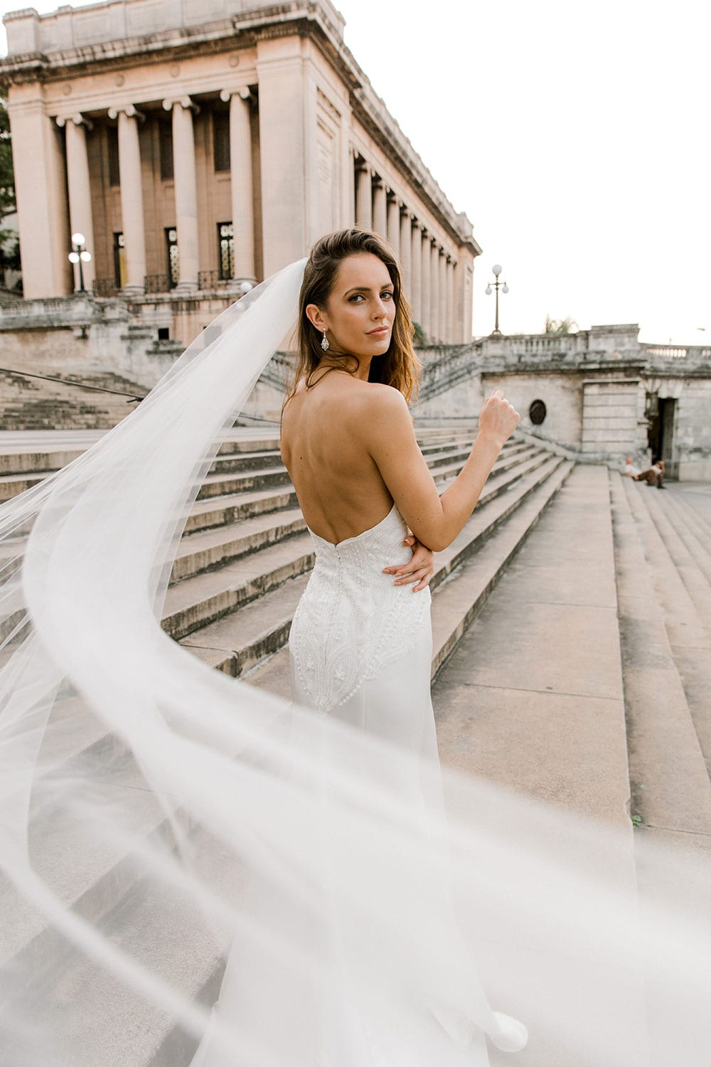 Model wearing Vinka Design Elsa Wedding Dress, a Satin Princess Line Wedding Gown with bodice on steps in Havana facing away with veil flowing in the breeze facing camera