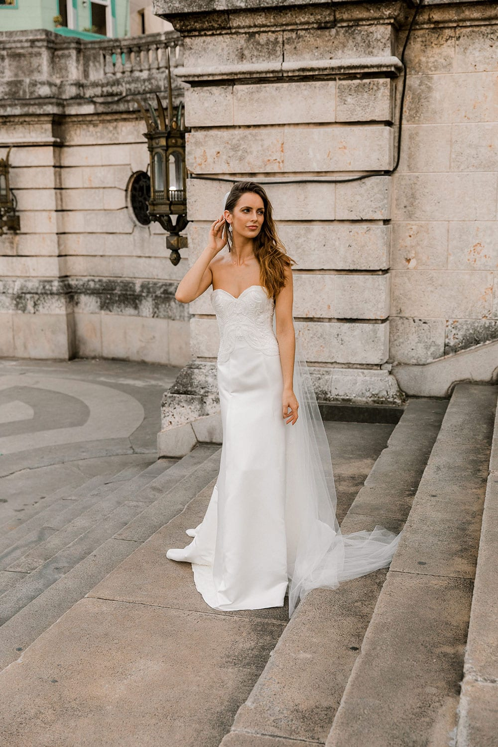 Model wearing Vinka Design Elsa Wedding Dress, a Satin Princess Line Wedding Gown with bodice in Havana walking up old steps