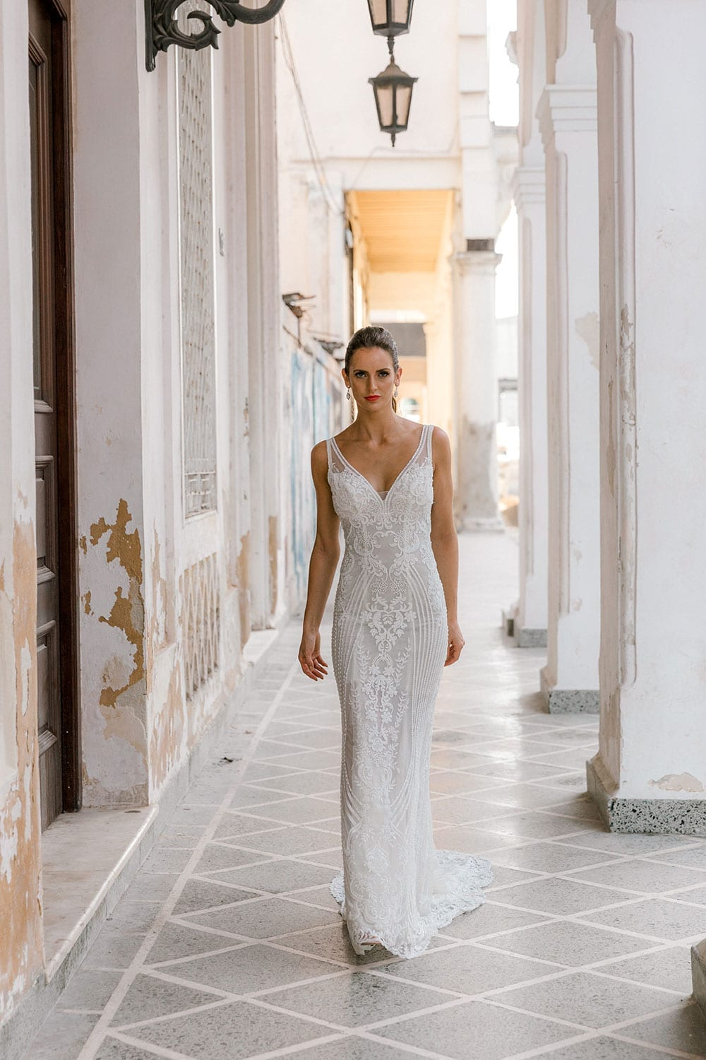 Model wearing Vinka Design Indi Wedding Dress, a Lace Fitted Wedding Gown walking through the streets of Havana
