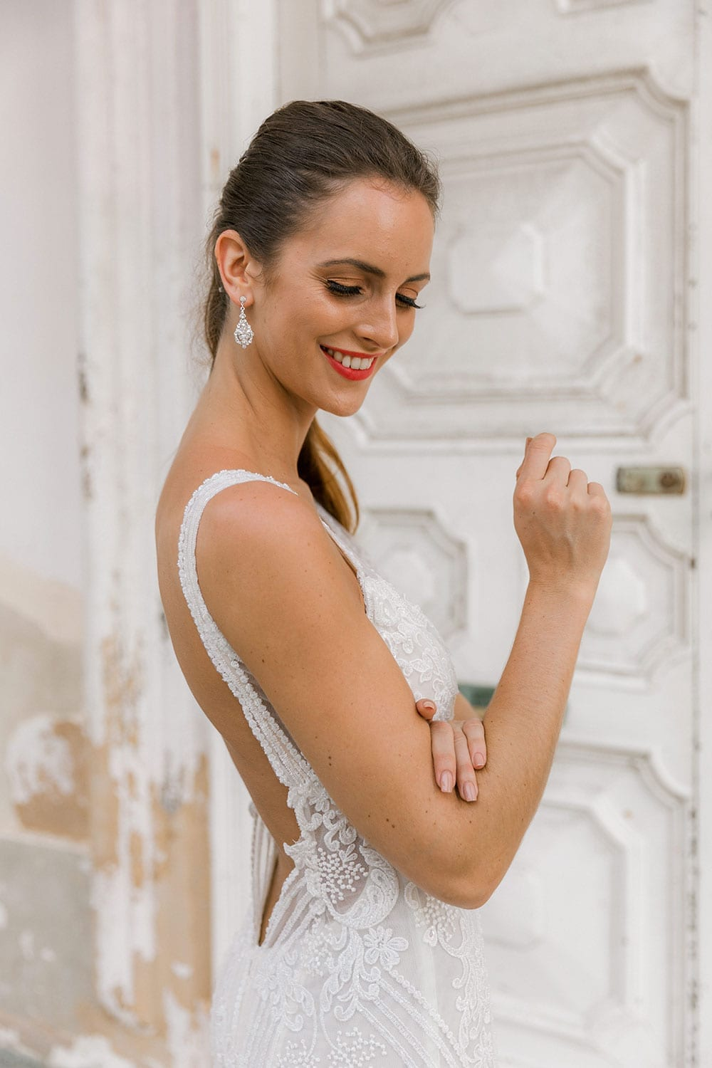 Model wearing Vinka Design Indi Wedding Dress, a Lace Fitted Wedding Gown close up showing low back posed in beautiful Havana