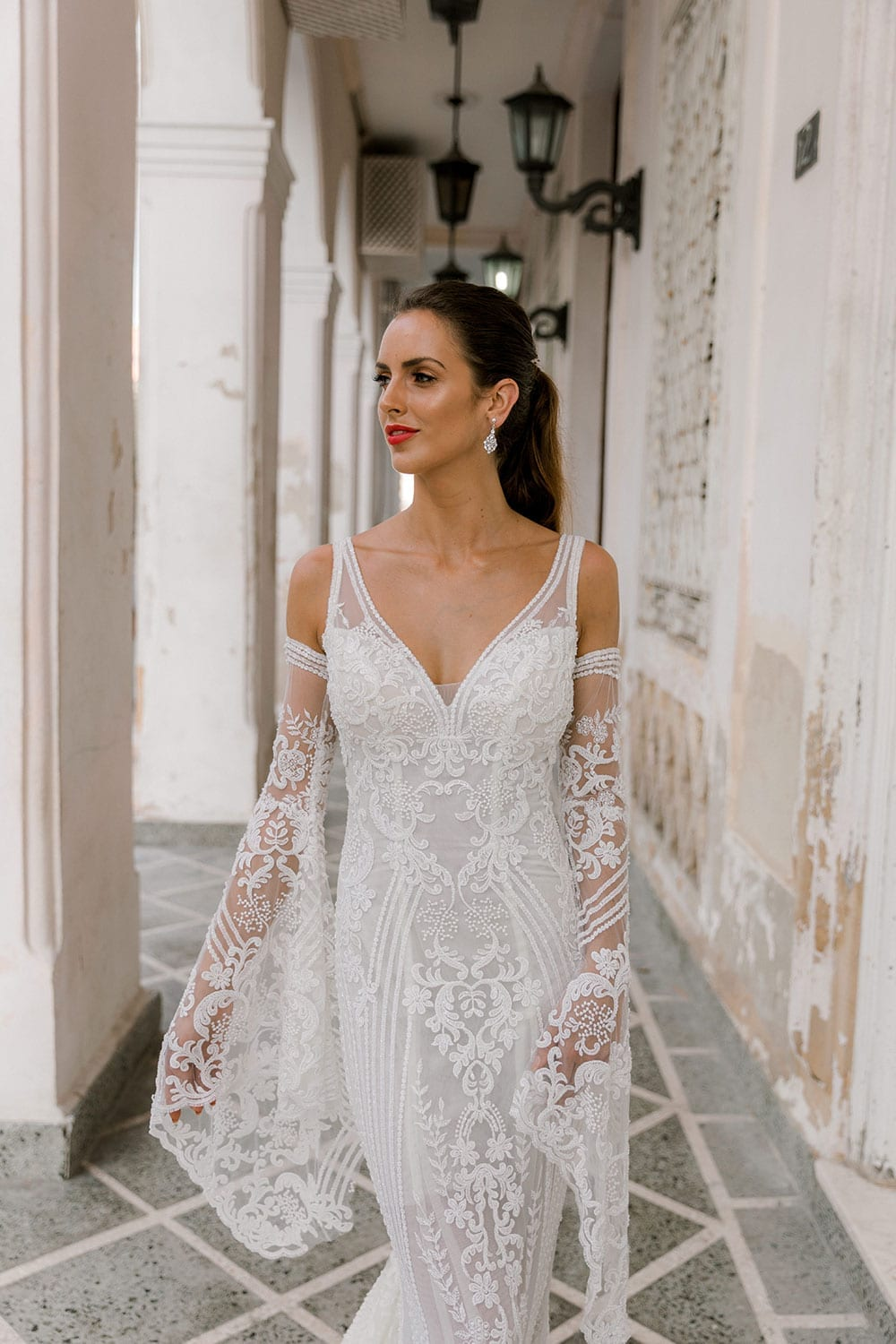 Model wearing Vinka Design Indi Wedding Dress, a Lace Fitted Wedding Gown in a walkway of old Havana