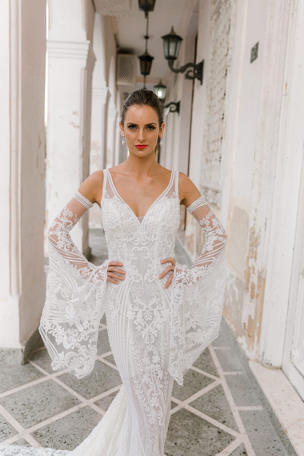 Model wearing Vinka Design Indi Wedding Dress, a Lace Fitted Wedding Gown in a walkway of old Havana hands on hips