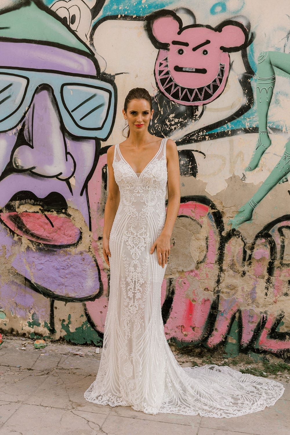 Model wearing Vinka Design Indi Wedding Dress, a Lace Fitted Wedding Gown in front of street art in Havana