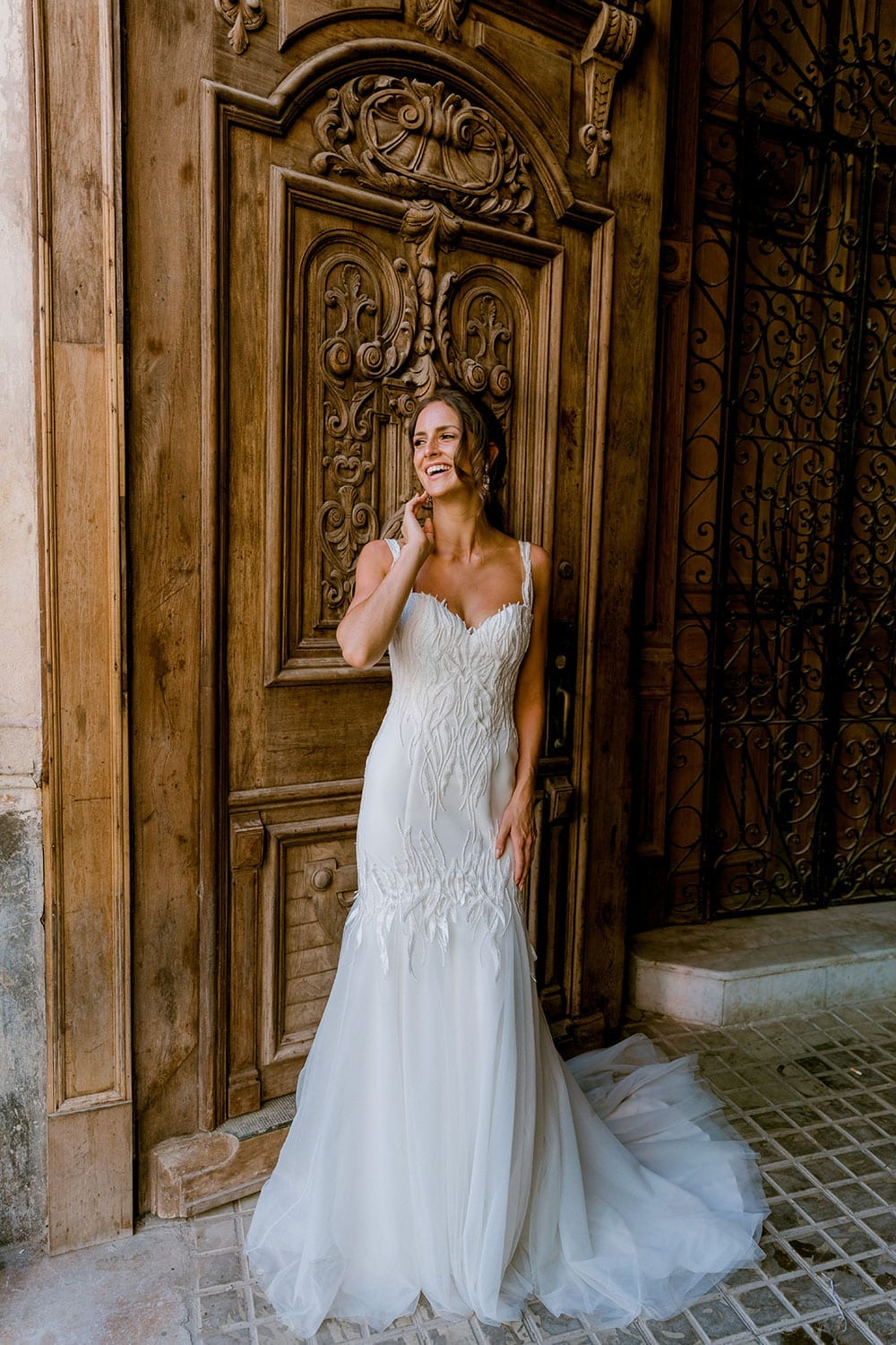 Model wearing Vinka Design Irina Wedding Dress, a n Embroidered Mermaid Lace Wedding Gown in front of a large old wooden door in Havana