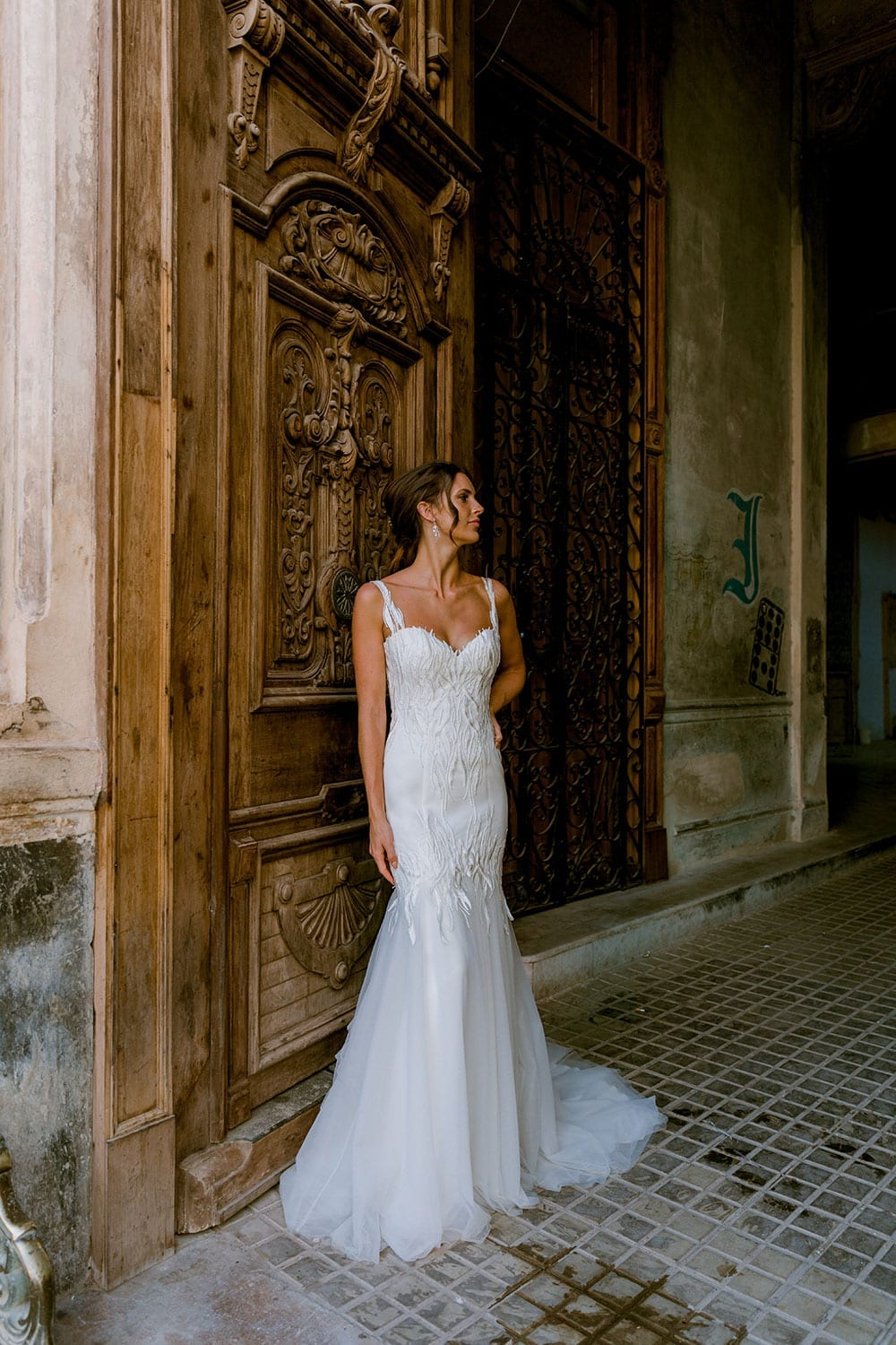 Model wearing Vinka Design Irina Wedding Dress, a n Embroidered Mermaid Lace Wedding Gown in front of a large old open wooden door in Havana