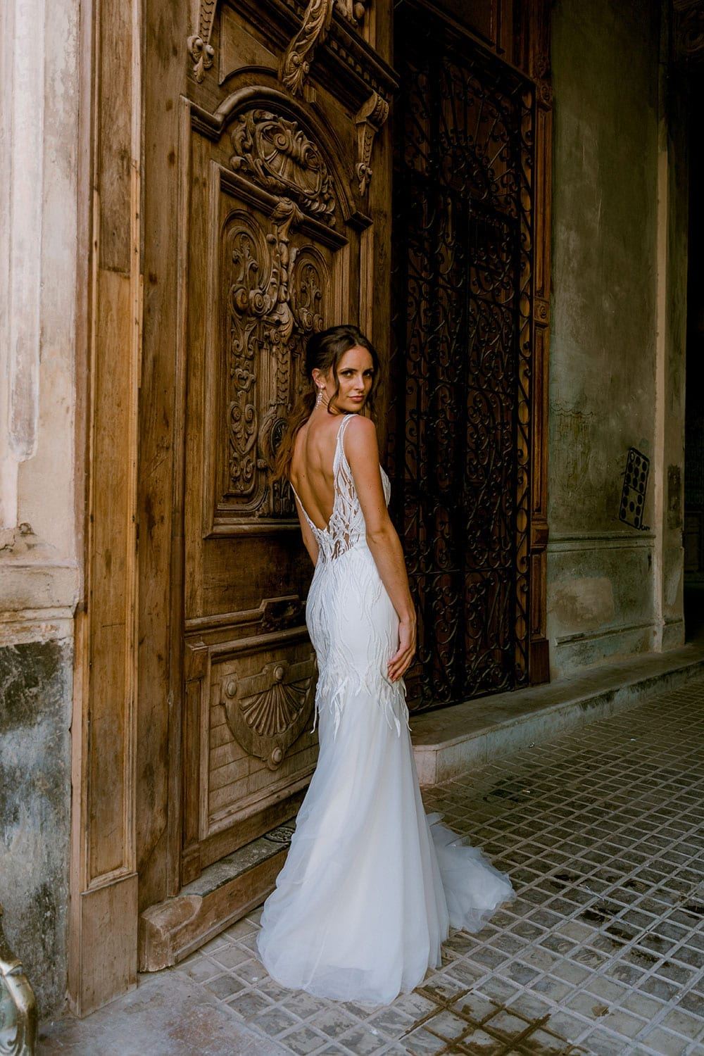 Model wearing Vinka Design Irina Wedding Dress, a n Embroidered Mermaid Lace Wedding Gown in front of a large old open wooden door in Havana facing inwards to reveal back of dress