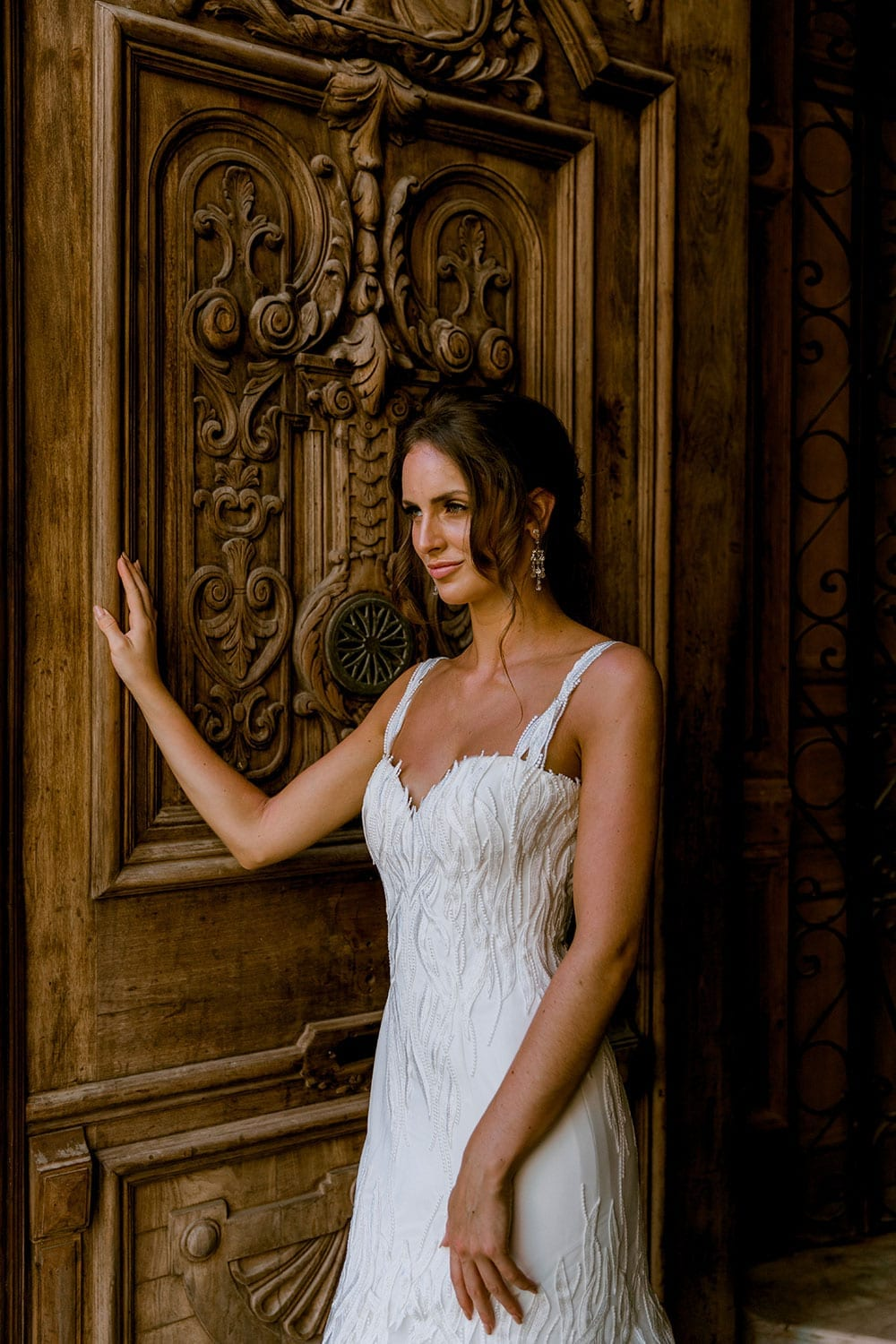 Model wearing Vinka Design Irina Wedding Dress, a n Embroidered Mermaid Lace Wedding Gown in front of a large old open wooden door in Havana close up