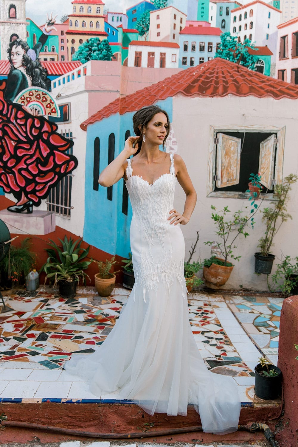 Model wearing Vinka Design Irina Wedding Dress, a n Embroidered Mermaid Lace Wedding Gown in front of colourful mural in Havana