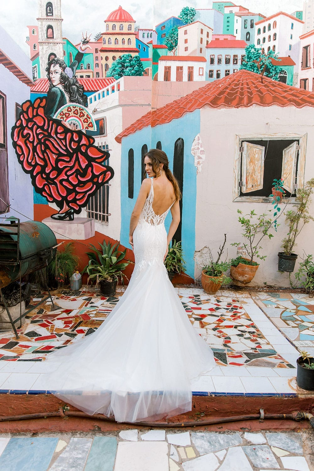 Model wearing Vinka Design Irina Wedding Dress, a n Embroidered Mermaid Lace Wedding Gown in front of colourful mural in Havana facing away to show back of dress