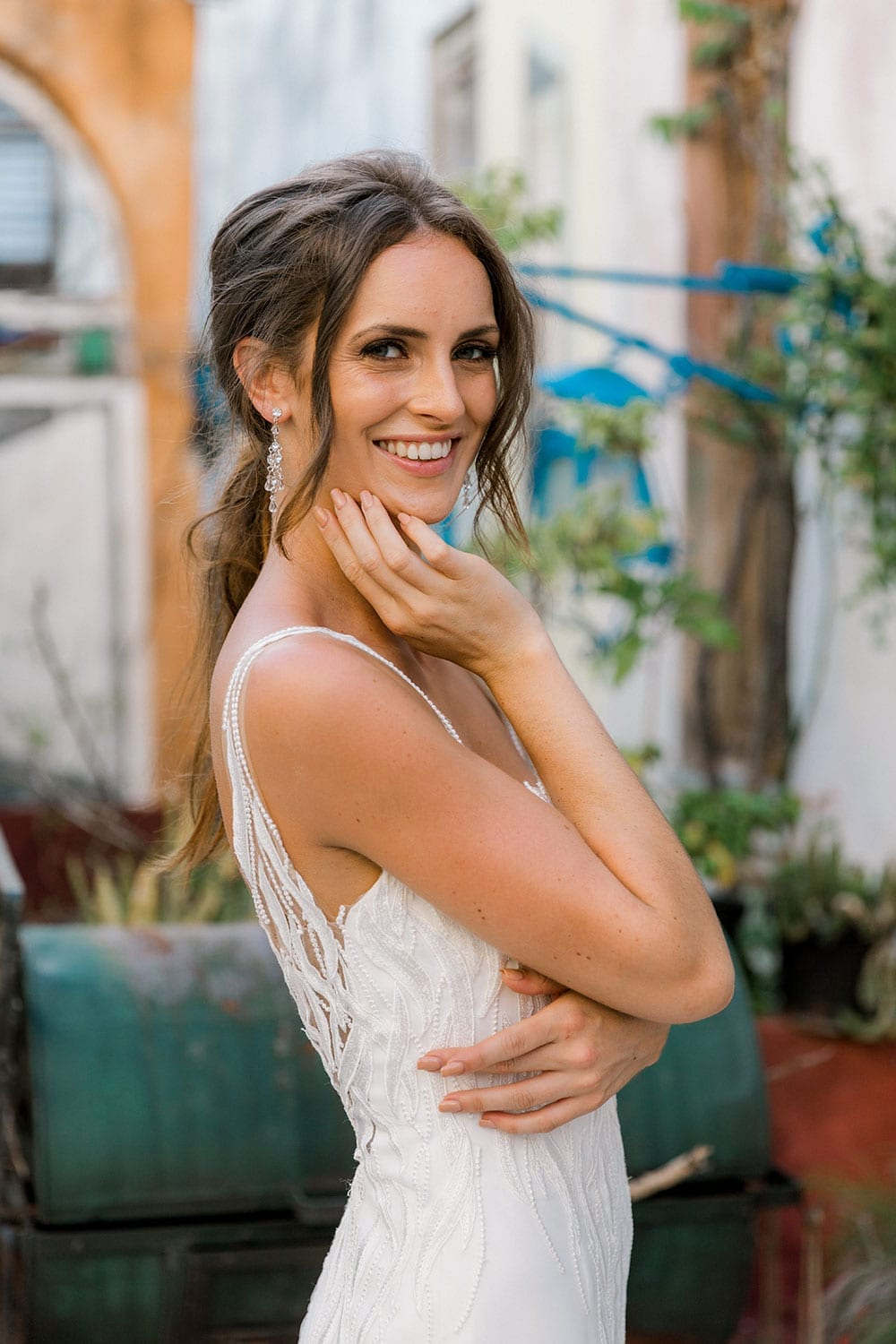 Model wearing Vinka Design Irina Wedding Dress, a n Embroidered Mermaid Lace Wedding Gown in front of colourful mural in Havana close up