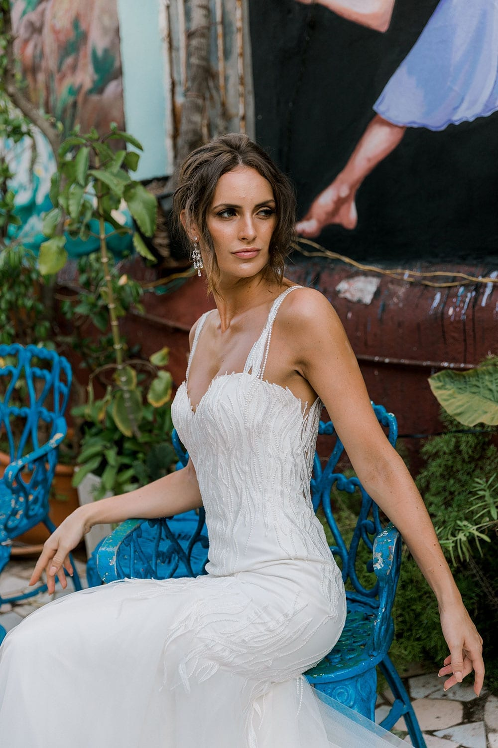 Model wearing Vinka Design Irina Wedding Dress, a n Embroidered Mermaid Lace Wedding Gown in front of colourful mural in Havana close up seated