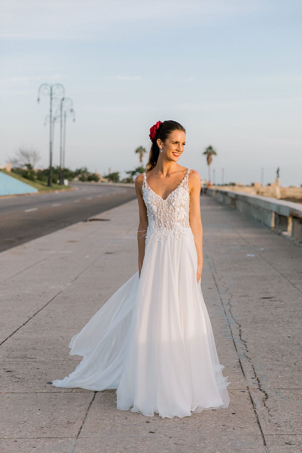 Model wearing Vinka Design Iris Wedding Dress, a Silk Chiffon Wedding Gown posed on a paved walkway in Havana looking to the side