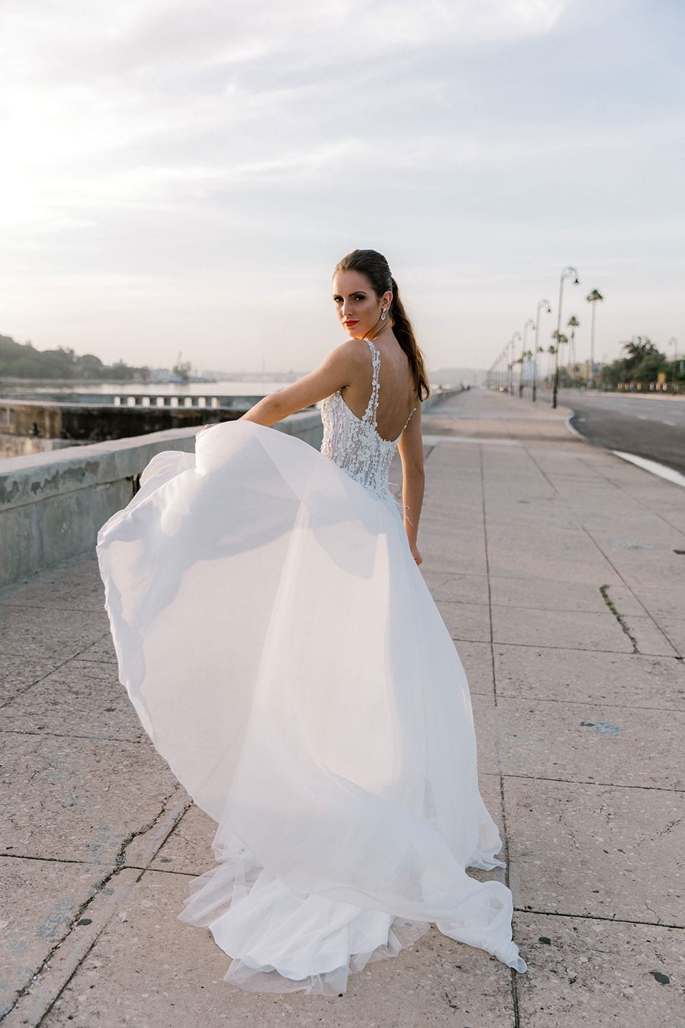 Model wearing Vinka Design Iris Wedding Dress, a Silk Chiffon Wedding Gown posed on a paved walkway in Havana raising layers of dress in the breeze