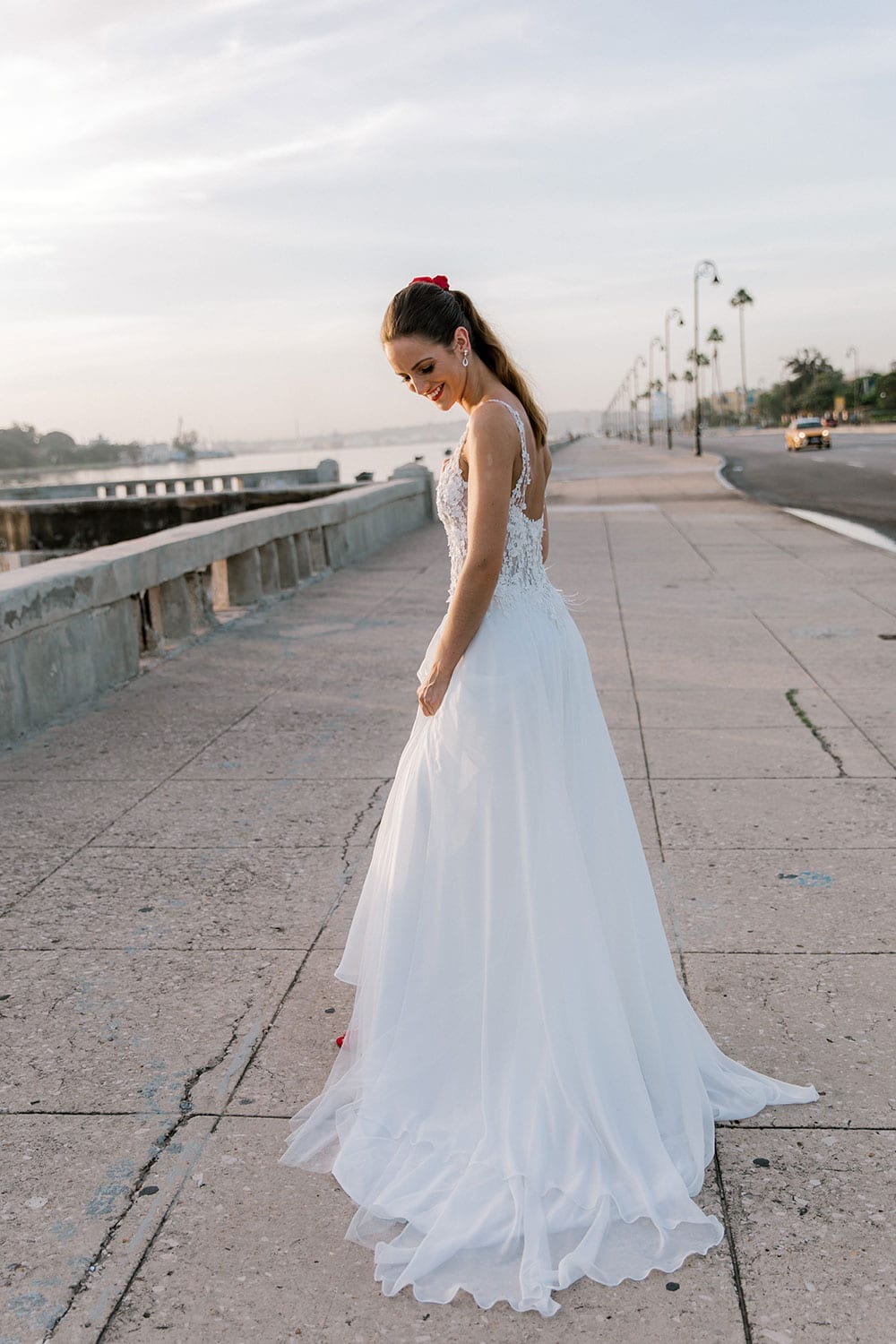 Model wearing Vinka Design Iris Wedding Dress, a Silk Chiffon Wedding Gown posed on a paved walkway in Havana with layers of dress showing movement