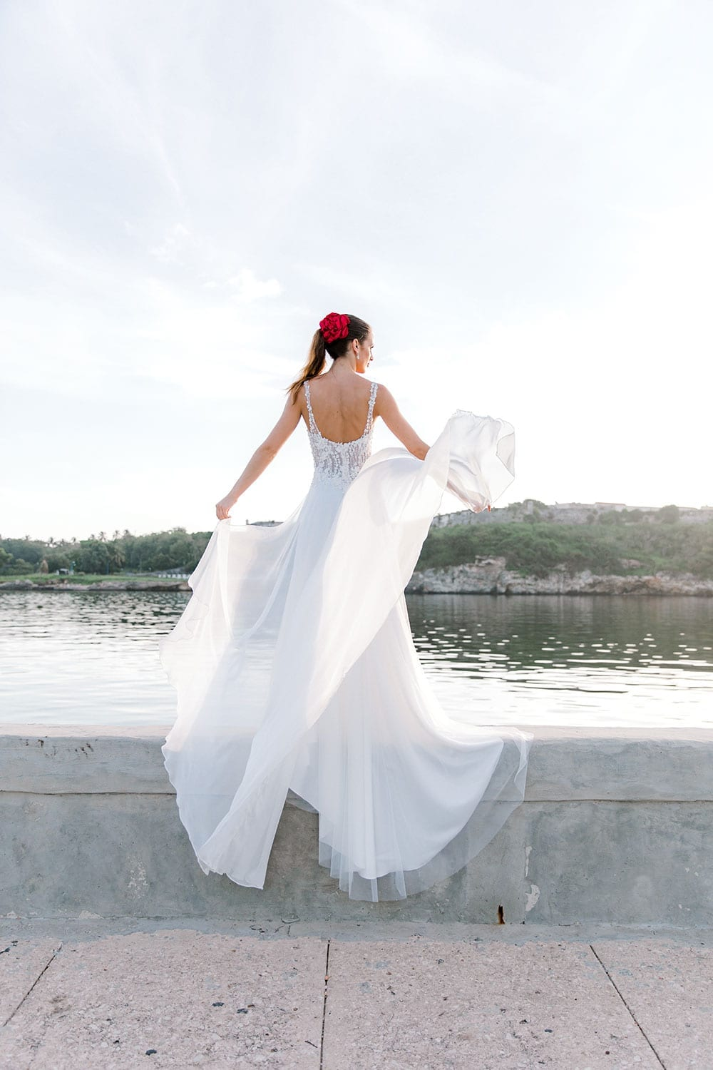 Model wearing Vinka Design Iris Wedding Dress, a Silk Chiffon Wedding Gown posed on a paved walkway in Havana facing away with dress flowing