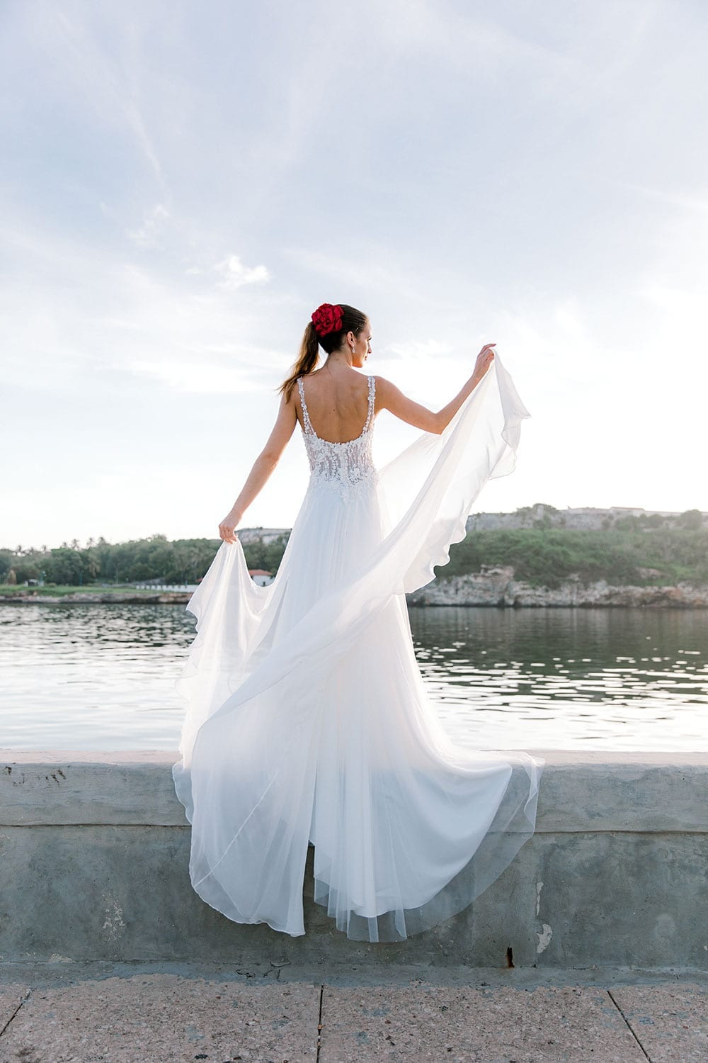Model wearing Vinka Design Iris Wedding Dress, a Silk Chiffon Wedding Gown posed on a paved walkway in Havana facing away with hand in the air and dress flowing