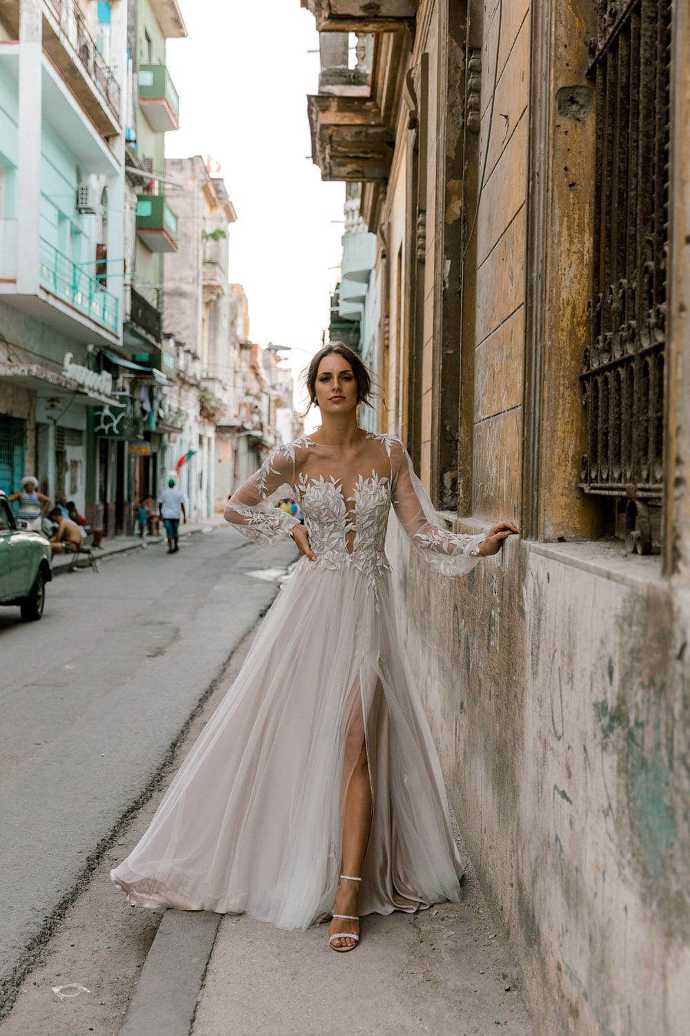 Model wearing Vinka Design Ivy Wedding Dress, a Silk and Tulle Wedding Gown with lace and Swarovski crystals walking on the streets of Havana