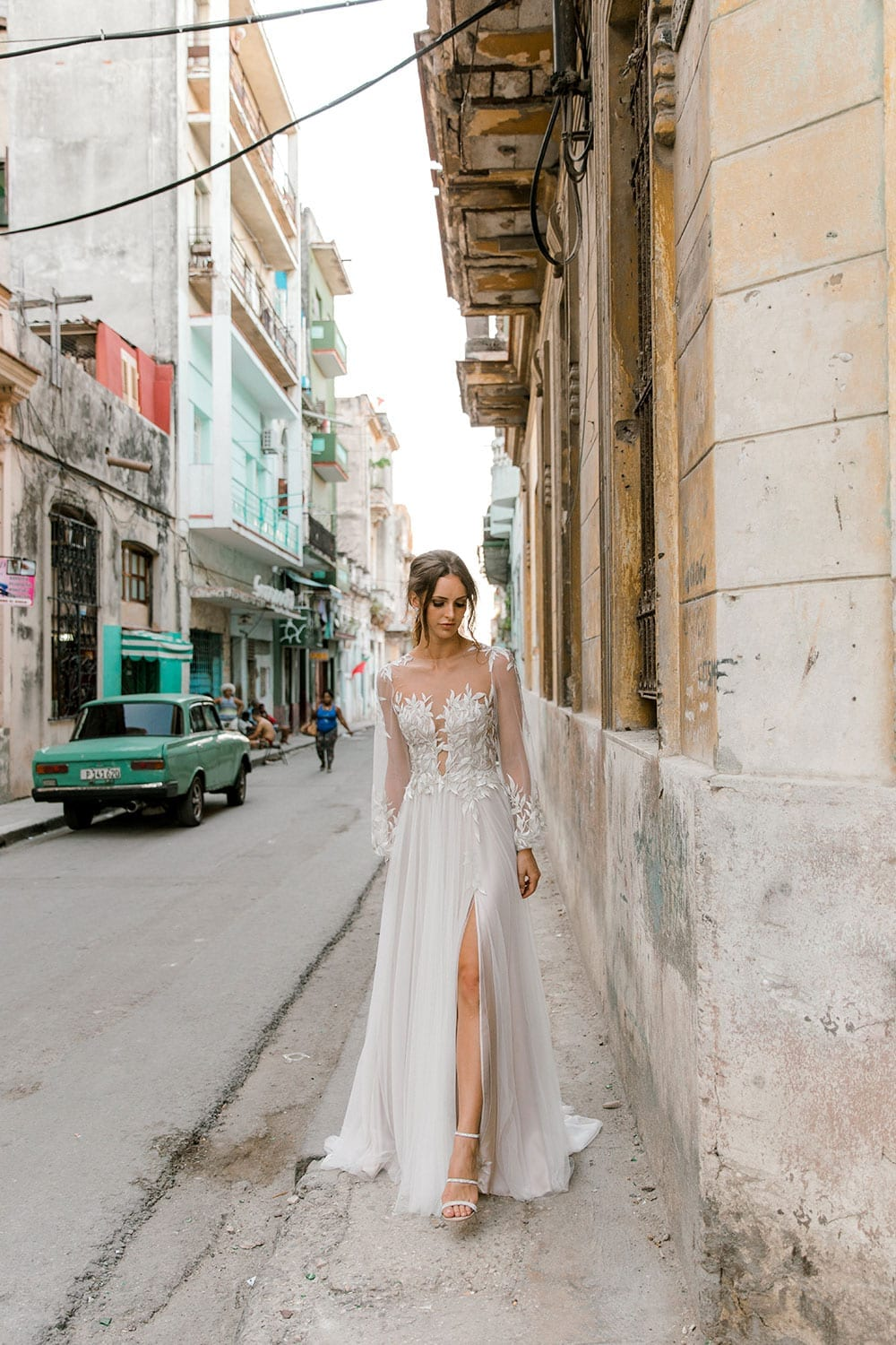Model wearing Vinka Design Ivy Wedding Dress, a Silk and Tulle Wedding Gown with lace and Swarovski crystals walking through the streets of Havana