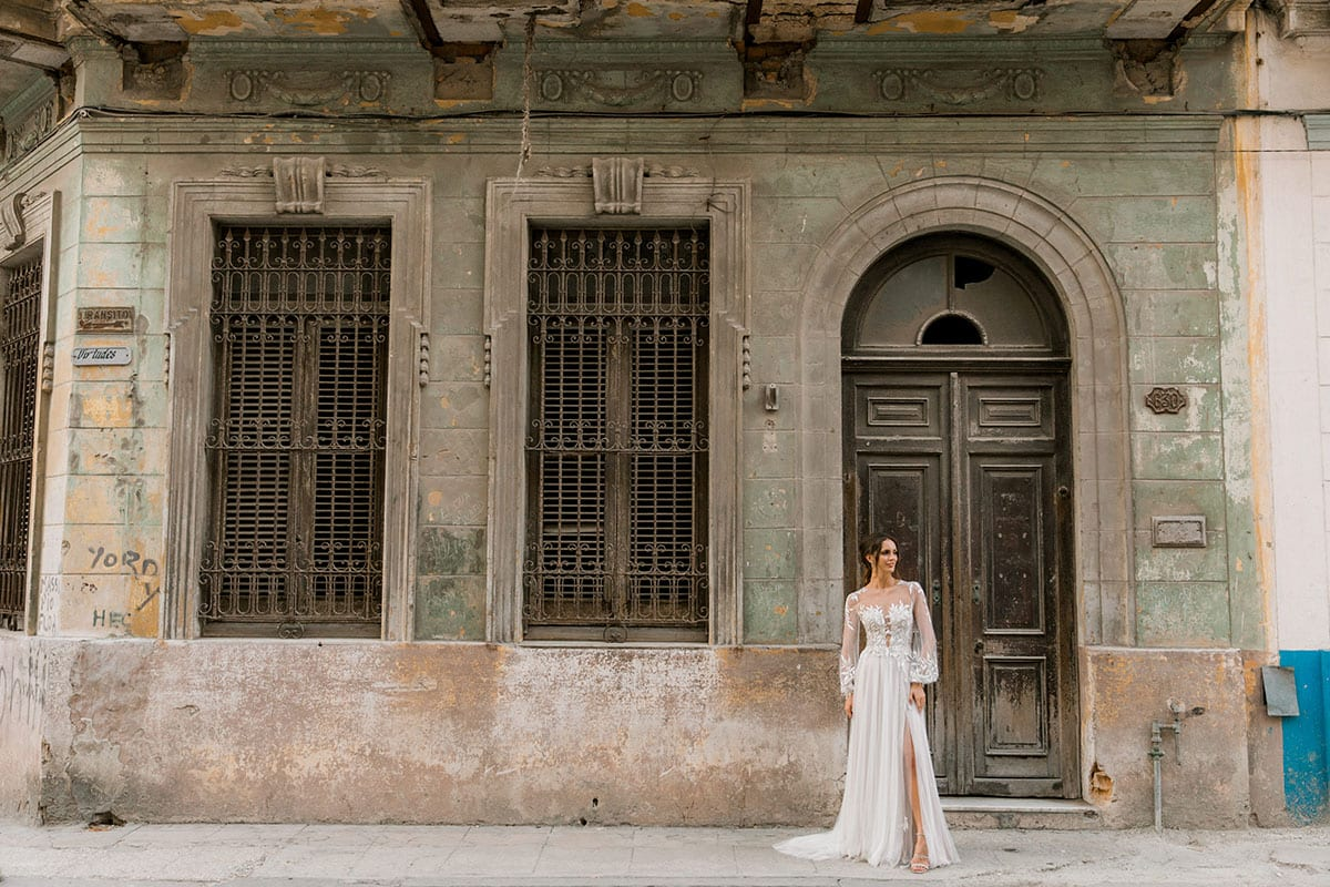 Model wearing Vinka Design Ivy Wedding Dress, a Silk and Tulle Wedding Gown with lace and Swarovski crystals in the streets of Havana with archways of buildings in the background