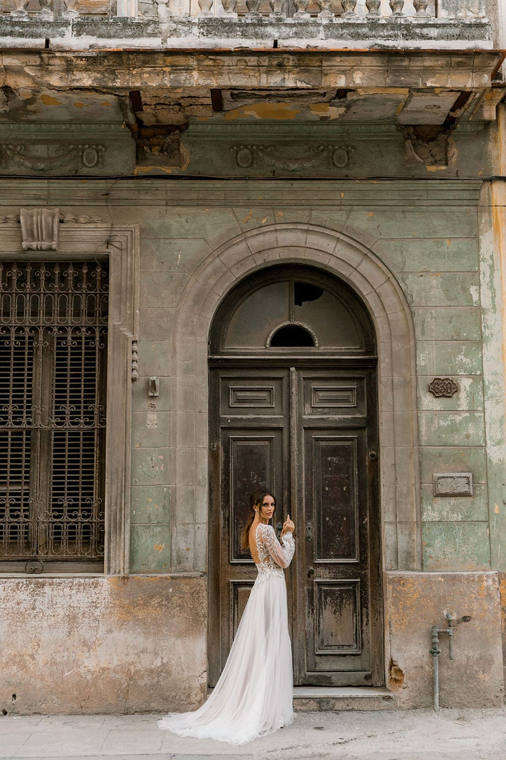 Model wearing Vinka Design Ivy Wedding Dress, a Silk and Tulle Wedding Gown with lace and Swarovski crystals in the streets of Havana with wooden arched doorway