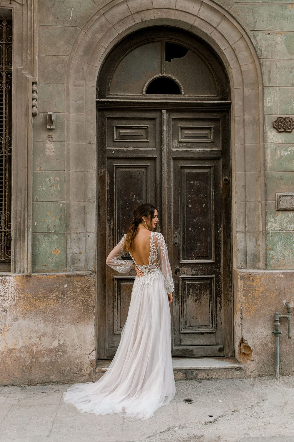Model wearing Vinka Design Ivy Wedding Dress, a Silk and Tulle Wedding Gown with lace and Swarovski crystals in the streets of Havana with wooden arched doorway in the background