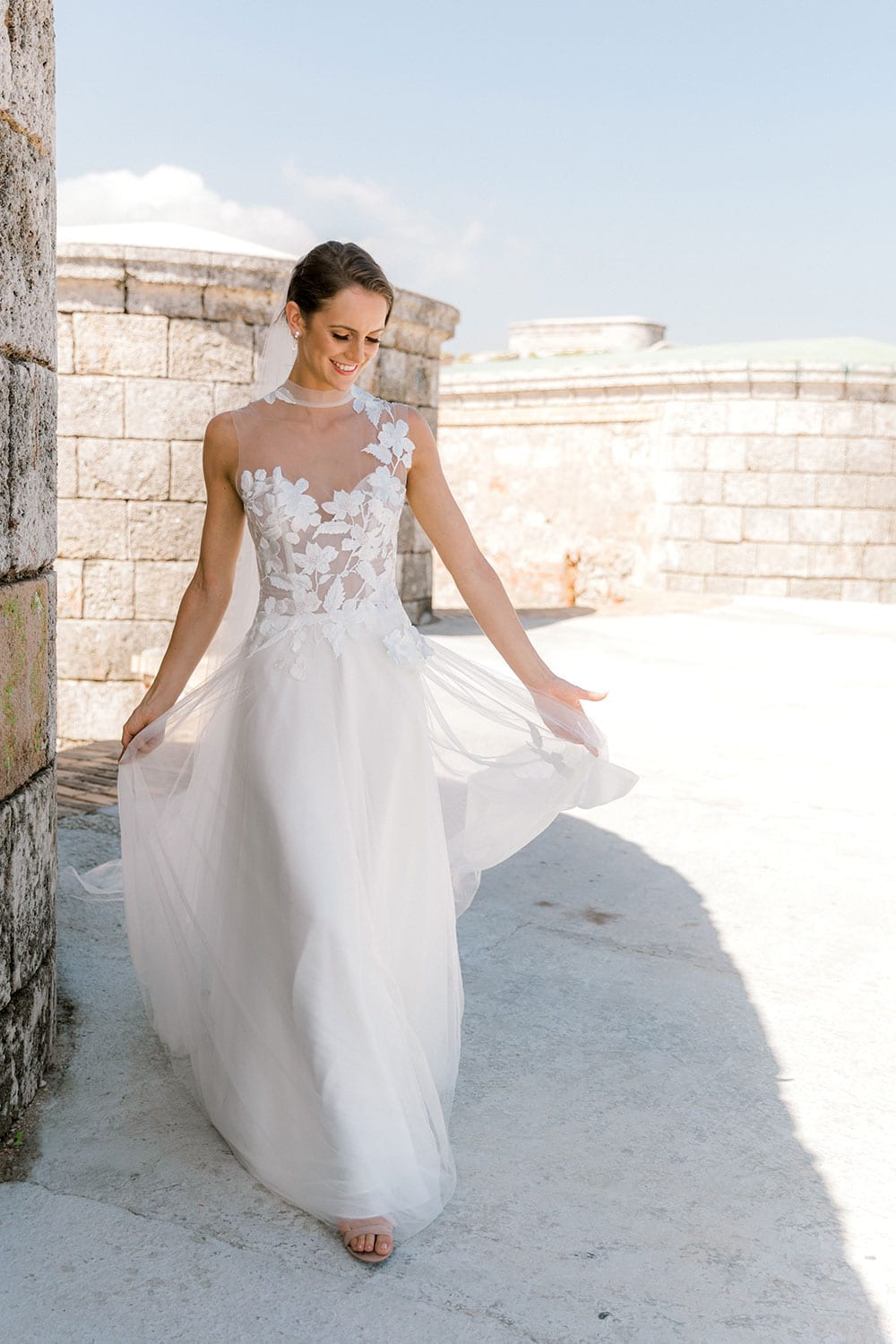 Model wearing Vinka Design Julia Wedding Dress, a High Neck Tulle Wedding Gown walking along a wall in Havana