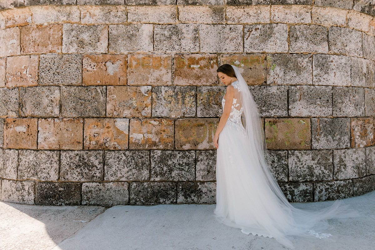 Model wearing Vinka Design Julia Wedding Dress, a High Neck Tulle Wedding Gown side on walking past an old wall in Havana