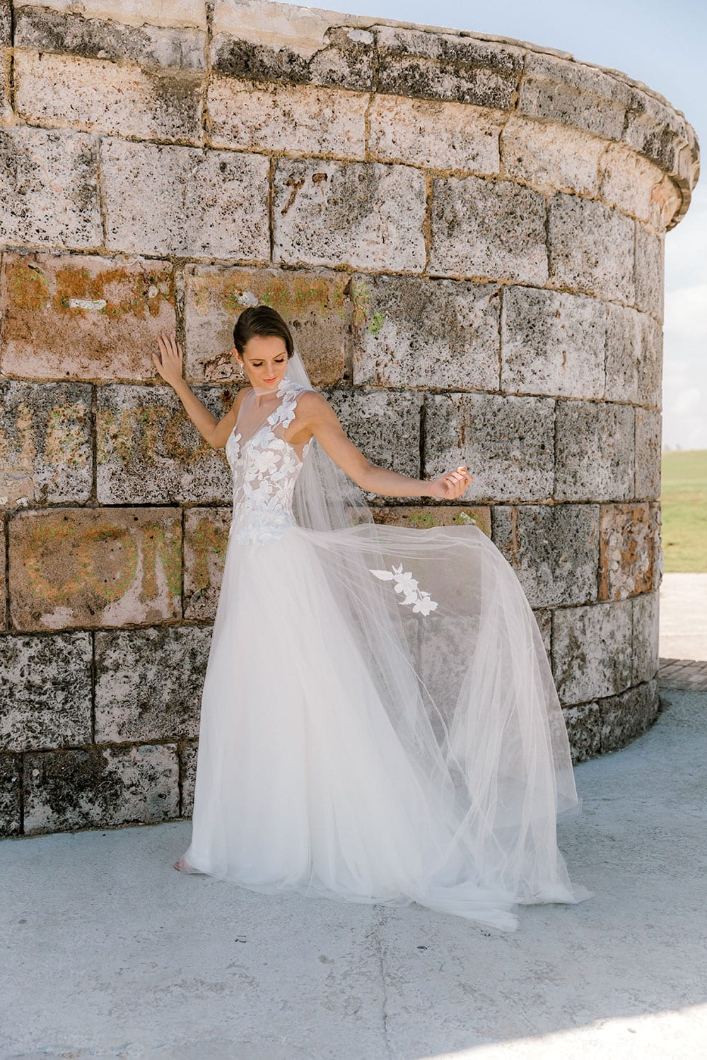 Model wearing Vinka Design Julia Wedding Dress, a High Neck Tulle Wedding Gown posed by an old wall in Havana