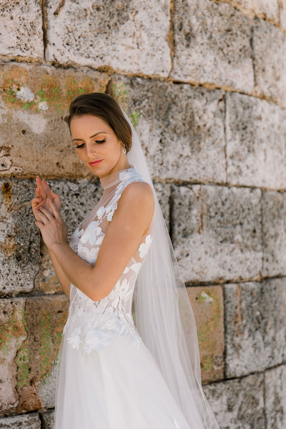Model wearing Vinka Design Julia Wedding Dress, a High Neck Tulle Wedding Gown leaning into an old wall in Havana