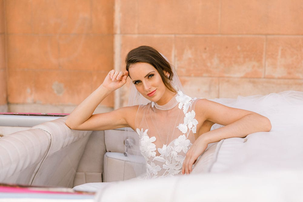 Model wearing Vinka Design Julia Wedding Dress, a High Neck Tulle Wedding Gown seated in a classic car in Havana