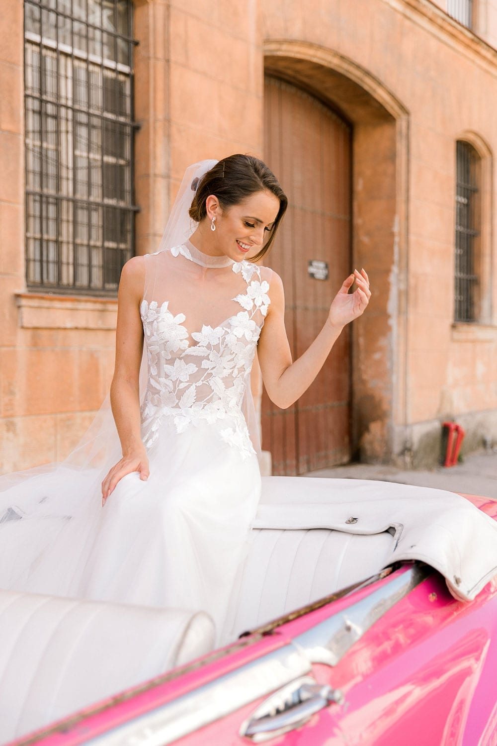 Model wearing Vinka Design Julia Wedding Dress, a High Neck Tulle Wedding Gown next to a classic car in Havana
