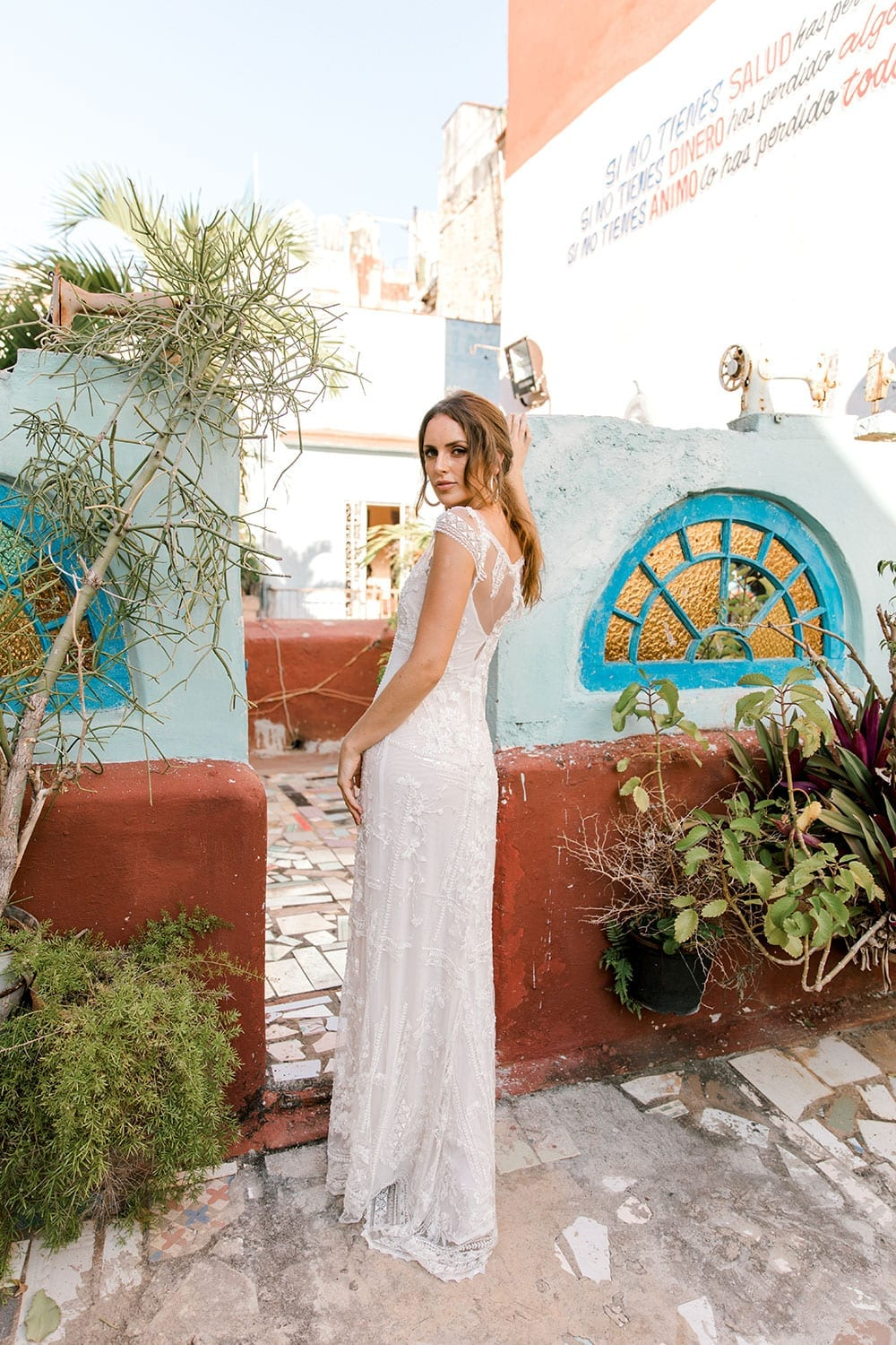 Model wearing Vinka Design Lola Wedding Dress, a Boat-Neck Lace Wedding Gown in the colourful streets and archways of Havana